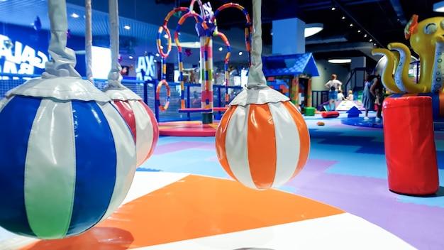 Immagine del primo piano della giostra colorata per bambini e dell'oscillazione nel parco giochi coperto con tappetini morbidi per la sicurezza dei bambini