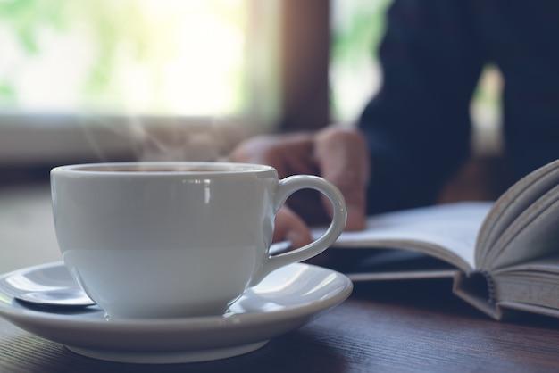 Immagine del primo piano della tazza di caffè con l'uomo che legge un libro come sfondo