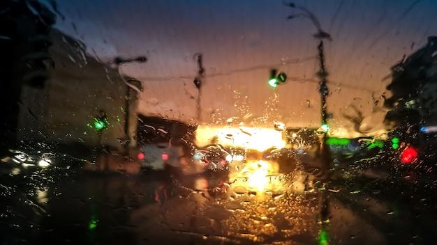 Immagine del primo piano delle goccioline sul parabrezza bagnato dell'auto sotto la pioggia alla luce del tramonto. colpo astratto di parabrezza bagnato e raggi di sole