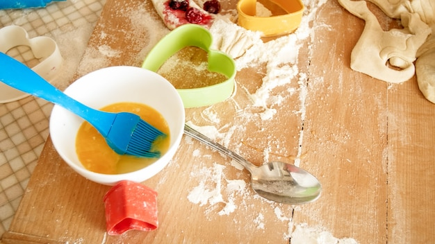 Immagine del primo piano dall'angolo alto sulla scrivania in legno ricoperta di farina, pasta, utensili da cucina e ingredienti per cucinare e cuocere in cucina