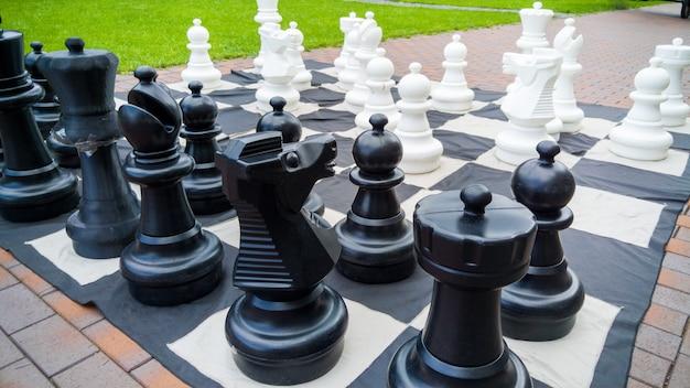 Immagine del primo piano della scacchiera gigante e delle figure di scacchi nel parco. intrattenimento e divertimento per la famiglia all'aria aperta