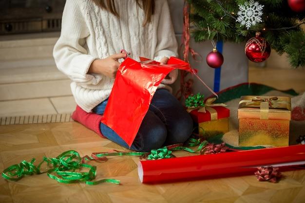 Immagine del primo piano della ragazza che avvolge i regali sotto l'albero di natale