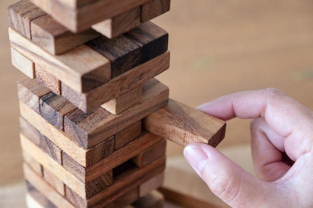 Immagine del primo piano di una mano che tiene e che gioca il gioco del blocco di legno della torre di caduta