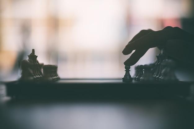 Immagine del primo piano di una mano che muove gli scacchi nel gioco della scacchiera