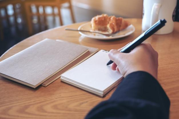 Immagine del primo piano di una mano che scrive sul taccuino in bianco con la tazza di caffè e il croissant sul tavolo nella caffetteria