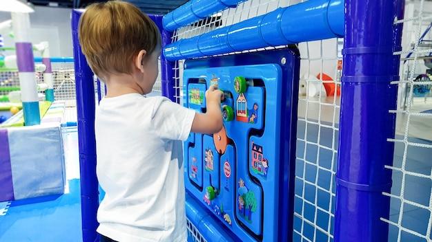 Immagine del primo piano del piccolo ragazzo del bambino che risolve il puzzle sul campo da gioco dei bambini al parco di divertimenti. concetto di bambini intelligenti e nuova generazione intelligente