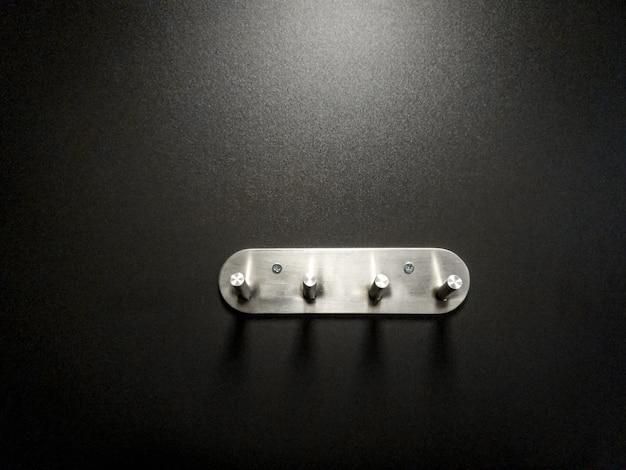 Immagine del primo piano dei ganci del gancio del metallo sulla parete nera nello spogliatoio