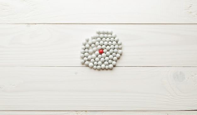 Immagine del primo piano di una sfera rossa tra tante bianche. concetto di differenza