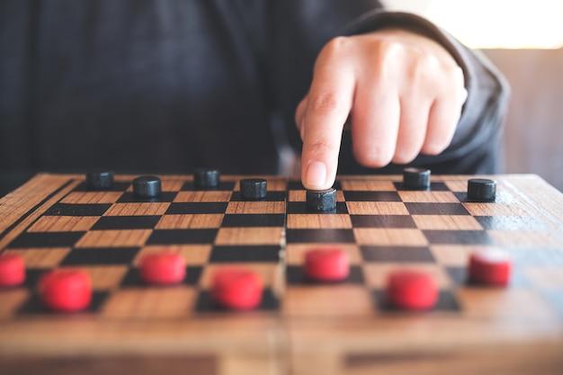 Immagine del primo piano di persone che giocano e pedine mobili in una scacchiera