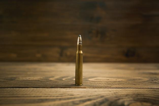 Immagine del primo piano del proiettile del fucile sulla vecchia scrivania in legno
