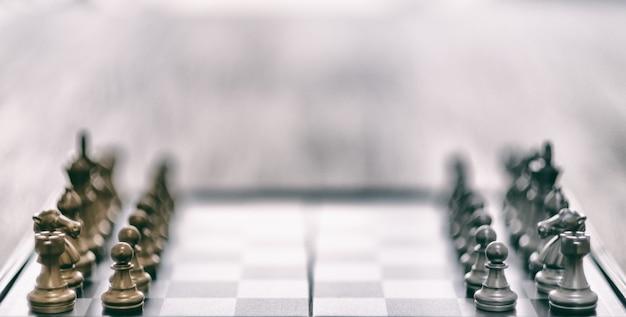 Immagine del primo piano di un set di scacchi color argento e oro sulla scacchiera