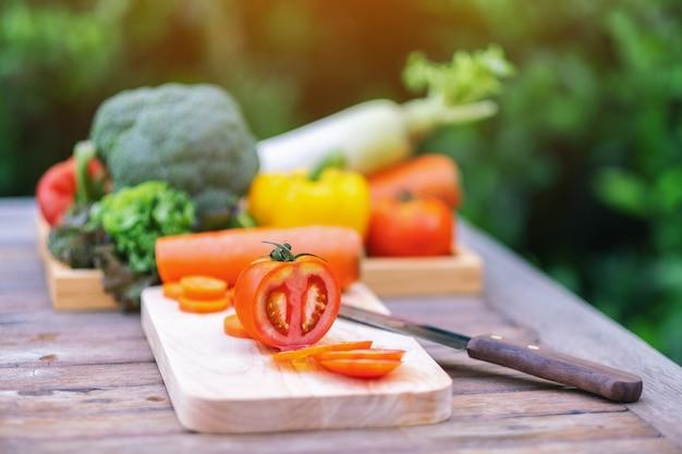 Immagine del primo piano di un pomodoro sul tagliere di legno con coltello e un vassoio di verdure miste sul tavolo
