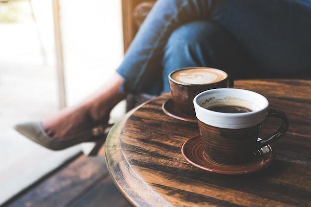 Un'immagine del primo piano di due tazze di caffè caldo del latte sulla tavola di legno d'annata con seduta della donna
