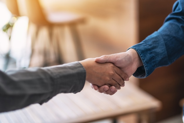 Immagine del primo piano di due persone che si stringono la mano