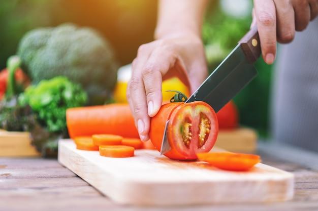 Immagine del primo piano di una donna che taglia e trita il pomodoro con un coltello su una tavola di legno