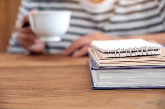 Primo piano immagine di una donna che beve caffè con libri e quaderni sulla tavola di legno