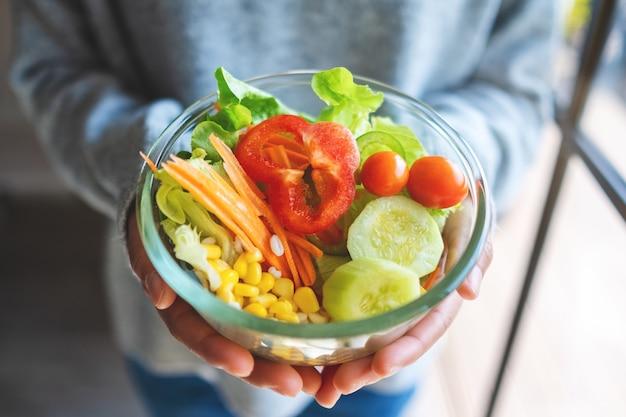 Immagine del primo piano di una donna che tiene in mano una ciotola di insalata di verdure miste fresche