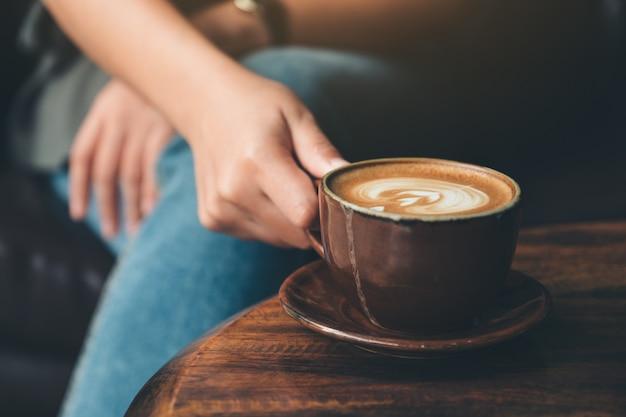 Immagine del primo piano di una donna che tiene un caffè della tazza sulla tavola di legno d'annata in caffè
