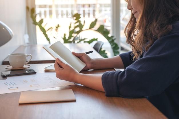 Immagine del primo piano di una donna che tiene e apre un taccuino in bianco con la tazza di caffè e le carte sul tavolo