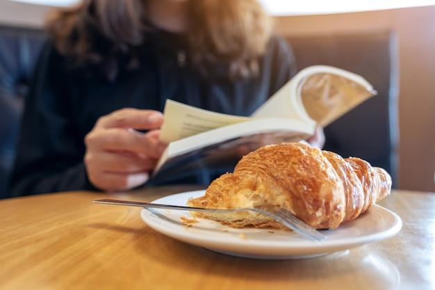 Primo piano immagine di una donna che mantiene e la lettura di un libro con un pezzo di croissant in un piatto e una tazza di caffè sul tavolo di legno
