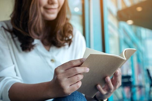 Immagine del primo piano di una donna che tiene e che legge un libro
