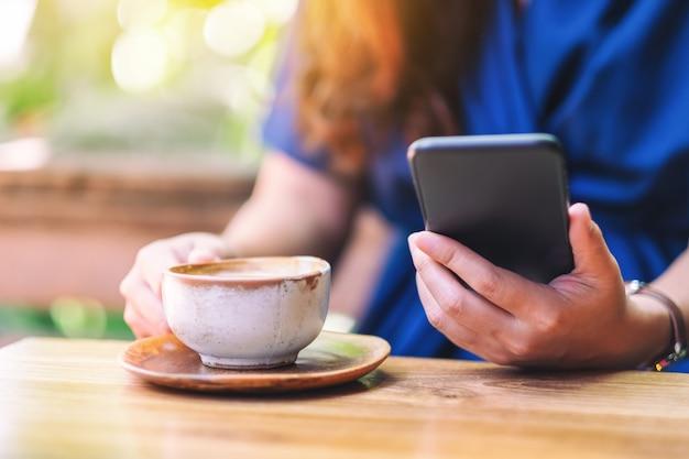 Immagine del primo piano di una donna che tiene e usa il telefono cellulare mentre beve caffè in giardino