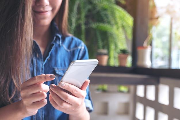 Immagine del primo piano di una tenuta della donna, usando e toccando uno smart phone