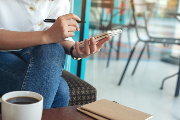 Immagine del primo piano di una donna che tiene e che scrive sul taccuino in bianco con la tazza di caffè sul tavolo