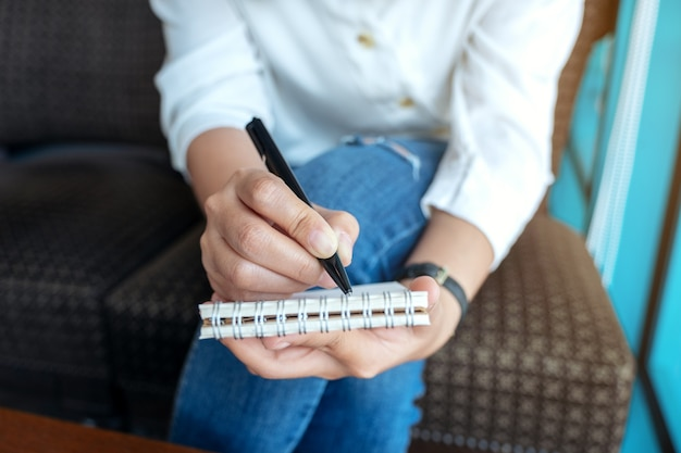 Immagine del primo piano di una donna che tiene e che scrive sul taccuino in bianco