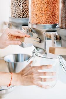 Primo piano immagine della donna versa lenticchie rosse in un barattolo di vetro dai distributori in un negozio di rifiuti zero