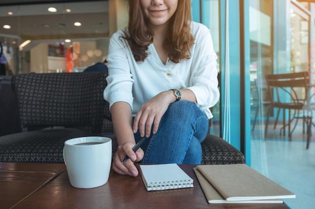 Immagine del primo piano di una donna che si prepara a scrivere sul taccuino in bianco con la tazza di caffè sulla tavola di legno