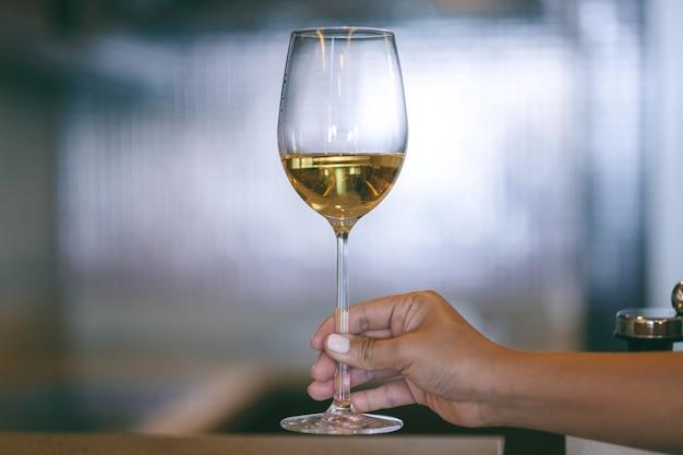Immagine del primo piano della mano di una donna che tiene un bicchiere di vino con sfondo sfocato