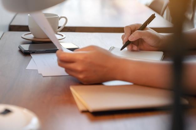 Immagine del primo piano delle mani della donna che tengono la carta del documento e che scrivono sul taccuino in bianco sulla tavola nella caffetteria