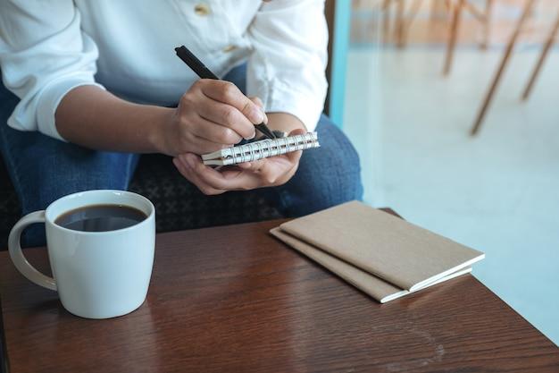 Immagine del primo piano delle mani di una donna che tengono e che scrivono sul taccuino in bianco con la tazza di caffè sulla tavola di legno