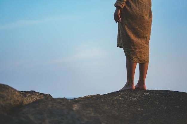 Immagine del primo piano della gamba di una donna in piedi sulla roccia sulla spiaggia