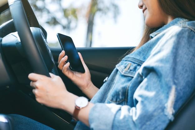 Immagine del primo piano di una donna che usa il telefono cellulare mentre guida un'auto
