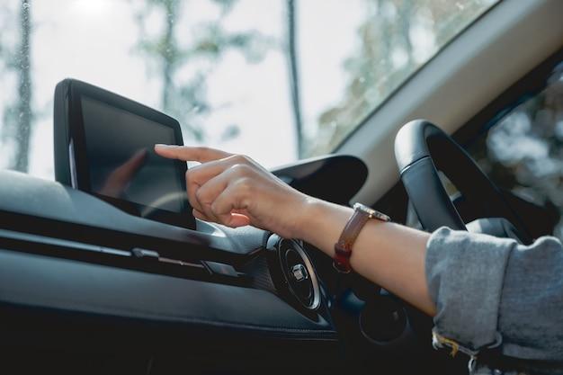Immagine in primo piano di una donna che usa e punta il dito sullo schermo di navigazione mentre guida l'auto
