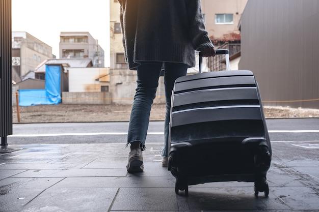 Immagine del primo piano di una donna che cammina durante il viaggio e trascina un bagaglio nero all'aria aperta
