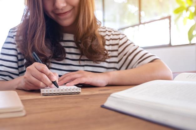 Immagine del primo piano di una donna che scrive sul taccuino in bianco e sui libri sulla tavola di legno durante l'apprendimento