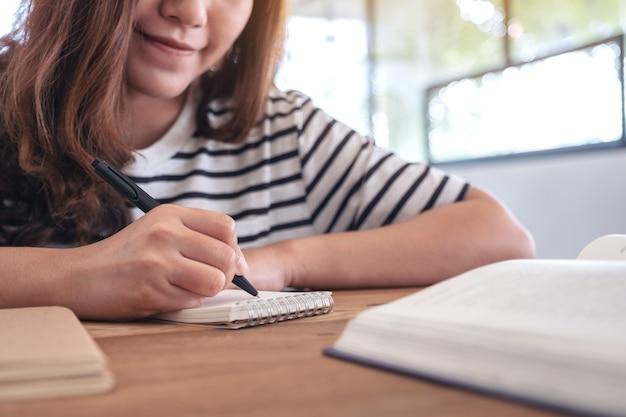 Immagine del primo piano di una donna che scrive sul taccuino in bianco con i libri sulla tavola di legno durante l'apprendimento