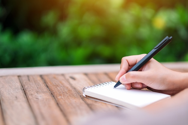 Immagine del primo piano di una donna che scrive su un taccuino bianco su un tavolo di legno all'aperto
