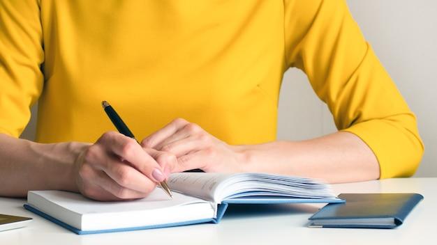 Immagine del primo piano di una donna che scrive su un taccuino in bianco bianco