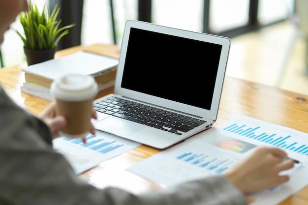 Immagine del primo piano di giovani imprenditrici che pianificano la strategia aziendale analizzando le prestazioni di vendita. relazione documenti e laptop sul tavolo