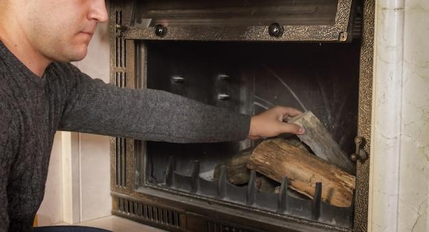 Immagine del primo piano del giovane che getta legna nel camino