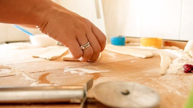 Immagine del primo piano della giovane donna che prende un pezzo di pasta e lo mette in forma di silicone per la cottura in forno. casalinga che prepara cupcakes a casa
