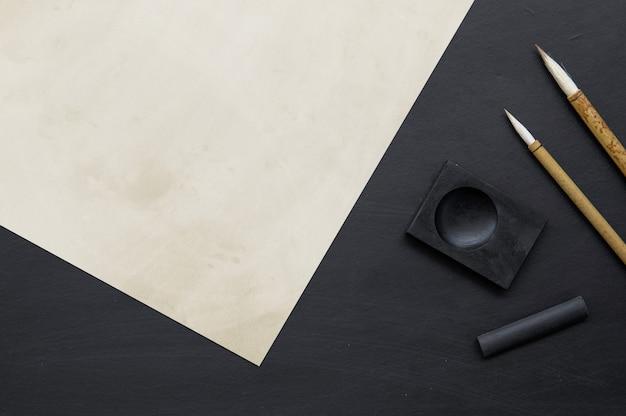 Pennello da scrittura tradizionale giapponese del primo piano sulla tavola nera .. piatto laici