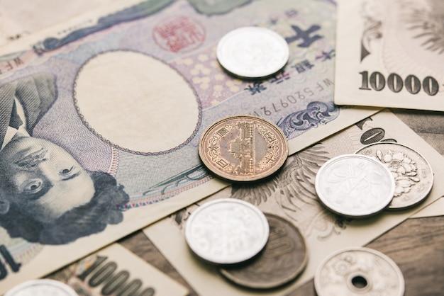 Primo piano delle banconote e monete di soldi di yen giapponesi sulla tavola