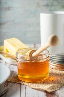 Primo piano di un barattolo di miele con il bastoncino di miele con il burro biologico fatto in casa sullo sfondo