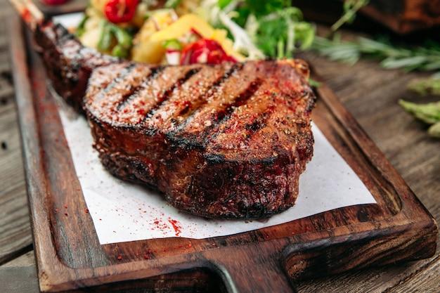 Primo piano sulla succosa bistecca di manzo alla griglia su una tavola di legno