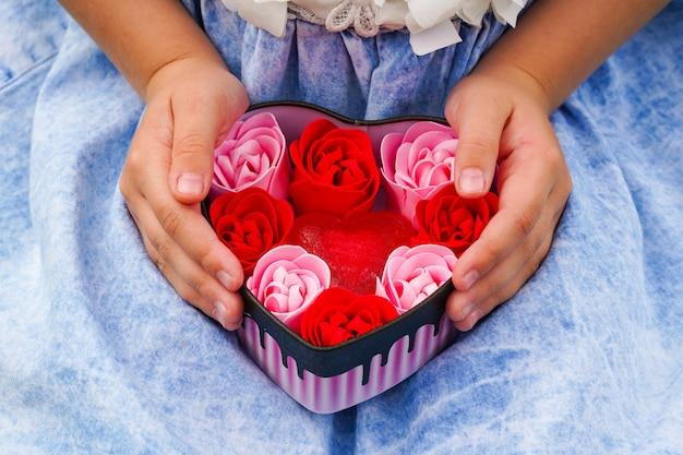 Primo piano delle mani dei bambini che tengono un regalo in un cuore rosa regali per il giorno di san valentino compleanno festa della mamma piatto laici simbolo di amore sfondo di san valentino